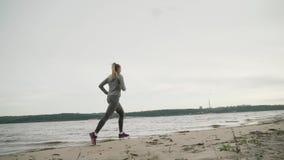 De looppas van de meisjesatleet langs de kust bewolking stock videobeelden