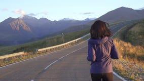 De looppas van de meisjesatleet op de weg aan de bergen bij zonsondergang stock videobeelden