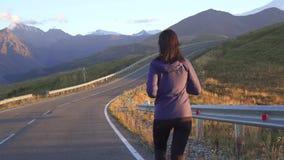 De looppas van de meisjesatleet op de weg aan de bergen bij zonsondergang dichte omhooggaand stock video