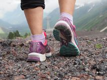 De loopschoenen van Saucony van mooie kleurrijke vrouwen, Tennisschoenen aan de benen van vrouwen brengen mening met bergen op de stock foto's