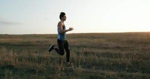 De lopende atleet die van de agentmens in openlucht het uitoefenen op bergweg opleiden bij zonsondergang in verbazende landschaps stock footage