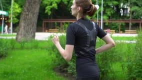 De lopende atleet die van de agentvrouw in openlucht het uitoefenen op parkweg opleiden bij zomer Langzame motie stock footage