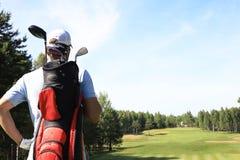 De lopende en dragende zak van de golfspeler op cursus tijdens de zomerspel het golfing stock foto's