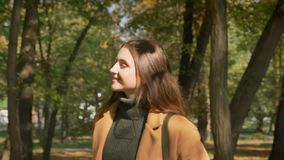 De lopende Kaukasische zwart-haired vrouw glimlacht en met sunlights op haar gezicht en ontspant op parkgebied, aard stock footage