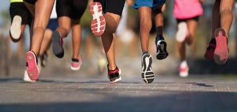 De lopende kinderen, jonge die atleten in in werking worden gesteld jonge geitjes stellen race in werking, die op stadsweg lopen stock afbeeldingen