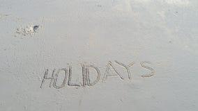 ` De los días de fiesta del ` escrito en la arena en la playa Fotos de archivo libres de regalías