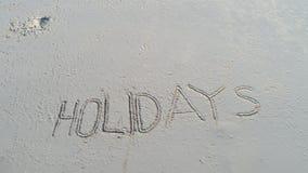` De los días de fiesta del ` escrito en la arena en la playa Fotografía de archivo libre de regalías