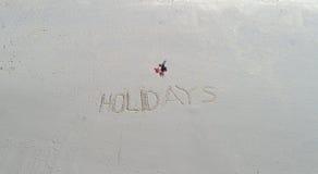 ` De los días de fiesta del ` escrito en la arena en la playa y la parte posterior de la mujer que pone en la toalla Fotos de archivo libres de regalías