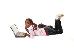 Muchacha adolescente con el ordenador portátil. Foto de archivo