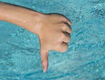 De los pulgares muestra abajo del hombre joven, adolescente con agua azul como backg Imágenes de archivo libres de regalías