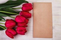 De los tulipanes rojos todavía de la hoja vida de papel Fotografía de archivo
