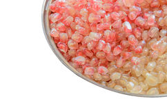 De losse zaden van het granaatappelfruit op roestvrije die kom op witte achtergrond wordt geïsoleerd Stock Foto