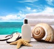 De lotion van Sunblock en handdoeken en oceaan stock foto