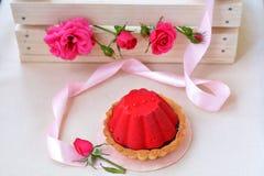 De lucht en de rode cake met chocolade dichtbij roze lint, namen toe Royalty-vrije Stock Afbeelding