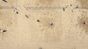 De lucht geschotene mensen spelen voetbal, badminton en volleyball bij de grond van zandsporten stock videobeelden
