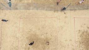 De lucht geschotene mensen spelen voetbal, badminton en volleyball bij de grond van zandsporten stock video