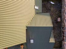 De lucht hoogste mening van groen shingled huisdak met nieuw klein zolder plastic venster stock afbeelding