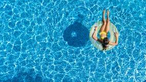 De lucht hoogste mening van meisje in zwembad van hierboven, jong geitje zwemt op opblaasbare ringsdoughnut, heeft het kind pret  Royalty-vrije Stock Fotografie