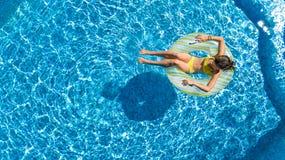 De lucht hoogste mening van meisje in zwembad van hierboven, jong geitje zwemt op opblaasbare ringsdoughnut, heeft het kind pret  Royalty-vrije Stock Afbeeldingen