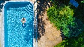 De lucht hoogste mening van meisje in zwembad van hierboven, jong geitje zwemt op opblaasbare ringsdoughnut, heeft het kind pret  Stock Afbeeldingen