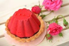 De lucht, rood cakehoogtepunt van chocolade dichtbij roze nam op lichtbruine, houten achtergrond toe Royalty-vrije Stock Fotografie