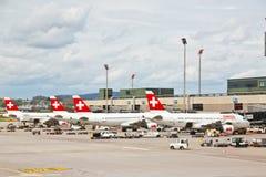 De luchtambachten van ZWITSER bij luchthaven 2 van Zürich Stock Afbeelding