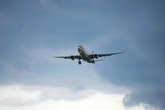 De Luchtbus A330-343 B-6527 luchtvaartlijnen Hainan Airlines komt uit een stormachtige hemel Royalty-vrije Stock Foto's