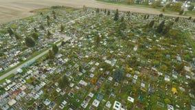 De luchtfoto die van begraafplaatskerkhof de grafstenen en de grafstenen van de graven wat tonen is met lange bloemen stock footage