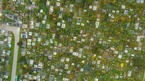 De luchtfoto die van begraafplaatskerkhof de grafstenen en de grafstenen van de graven wat tonen is met lange bloemen stock videobeelden