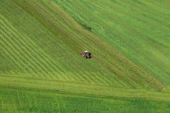 De luchtfoto van het landschap en de landbouwer van het weidegras in tractor die groen grasgebied na het besnoeiingsgras kan maai royalty-vrije stock foto's