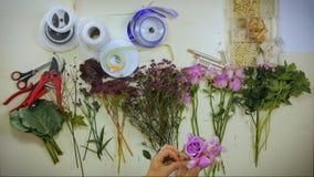 De luchthanden van een bloemist brengt een boeket van bloemen samen stock videobeelden