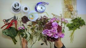 De luchthanden van een bloemist brengt een boeket van bloemen samen stock video