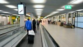 De Luchthaven Schiphol, passagiers van Amsterdam op de roltrap, stock video