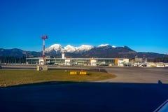 De Luchthaven van Ljubljana met tarmac, terminal en bergen op achtergrond stock afbeelding