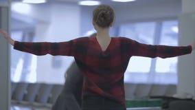 De luchthavenarbeider tast een jonge vrouw met handscanner in af de luchthaven stock footage