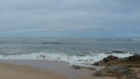 De luchthommel schoot het vliegen voorwaarts over zandig strand naar oceaan op donkere dag in Portugal stock video