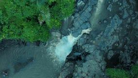 De luchtlengte van de mooie waterval met schuimend water, de grote rotsen en de groene installaties op Bali Indonesië 4k reizen w stock video