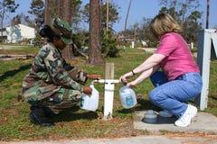De de Luchtmachtsergeant en dame vullen waterkruiken vanaf noodsituatiekraan royalty-vrije stock afbeelding