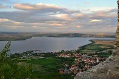 De luchtmening over dorp en meer onder wolken van een kasteel ruïneert Royalty-vrije Stock Afbeelding