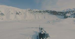 De luchtmening de skiërs gaat naar de helikopter in de sneeuwbergen stock video