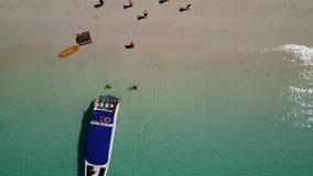 De luchtmening van een boot ontscheept toeristen op een mooi strand stock videobeelden