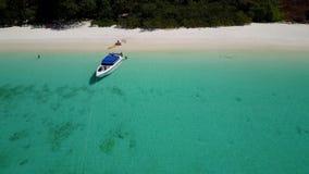 De luchtmening van een boot ontscheept toeristen op een mooi strand stock footage