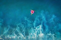 De luchtmening van het jonge vrouw zwemmen op het roze zwemt ring stock afbeelding