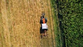 De luchtmening van maaidorser, tractor op hooigebied Landbouw en het oogsten Tarweproductie stock afbeeldingen