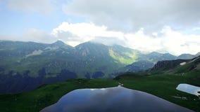De luchtmening van smaragdgroen meer hoog in de bergen in de bergen en de ravijnen overzien en Abchazië die betrekt lopen stock video