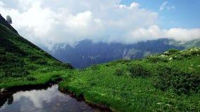 De luchtmening van smaragdgroen meer hoog in de bergen in de bergen en de ravijnen overzien en Abchazië die betrekt lopen stock footage