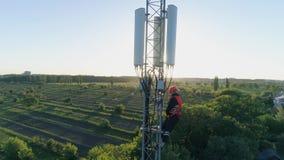 De luchtmening van telecommunicatietoren, technicus in veiligheidsvest en bouwvakker gebruikt mobiele telefoon bovenop cellulair stock videobeelden