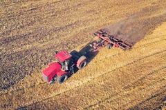 De luchtmeningshommel van oogstgebied met tractor maait droog gras De herfst geel gebied met een hooiberg na oogst hoogste mening royalty-vrije stock afbeeldingen
