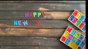 De luchtvideo van de tijdtijdspanne van de hand die van een kind een Gelukkig Nieuwjarenbericht in gekleurde blokletters op houte stock videobeelden