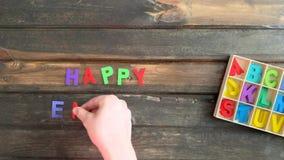 De luchtvideo van de tijdtijdspanne van de hand die van een kind Gelukkig Pasen-vakantiebericht in gekleurde blokletters op houte stock footage